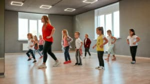 Group of little boys and girls dancing while having choreography class in the dance studio. Female dance teacher and children